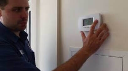 Repairman fixing thermostat